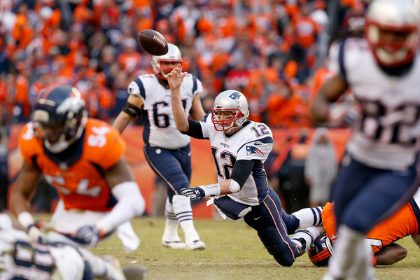 Tom Brady passes the ball while falling down